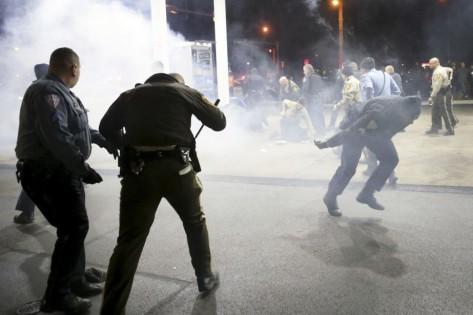 Les policiers tentant de contenir les manifestants à la station-service à l'aide de gaz poivré.